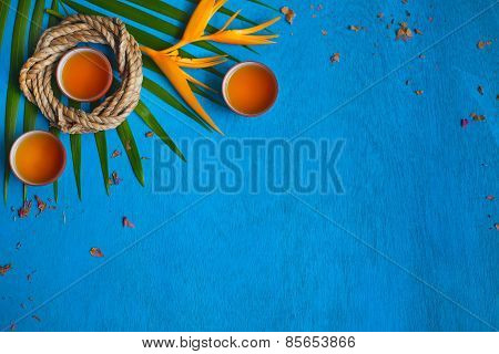 Three Teacups With Shuck, Coil Of Rope, Green Leaves And Yellow Flower On Blue Wooden Background.