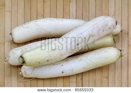 Closeup photo of white Radish (Daikon) on a wooden background