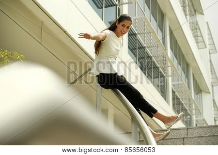 Cheerful Business Woman Going Downstairs Sliding On Rail For Joy