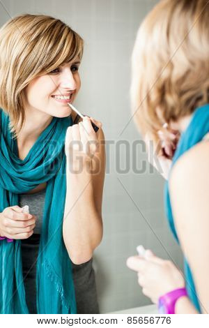 Pretty, young woman applying mascara /eyeshadows in front of a mirror