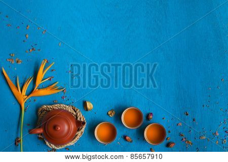 Clay Teapot, Three Teacups With The Rope, Shuck And Rose Buds On Blue Wooden Background.