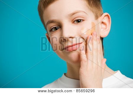 Smiling Boy With Adhesive Plaster On His Cheek