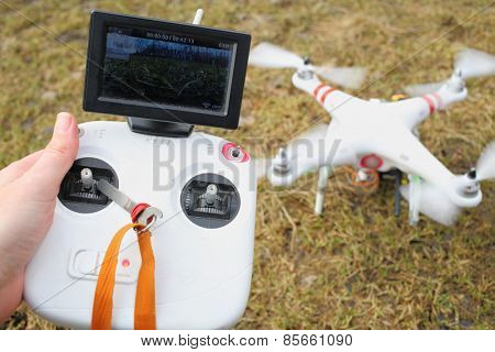 MOSCOW - MAR 11, 2014: Control panels in hand and quadcopter with propellers