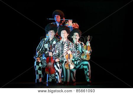 MOSCOW - MAR 12, 2014: Four funny men Taper-show: dancing on the strings in black wigs and costumes with musical instruments on stage of the Palace on Yauza