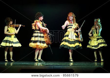 MOSCOW - MAR 12, 2014: Four actors Taper-show: dancing on the strings dressed in female clothes with musical instruments on stage of the Palace on Yauza