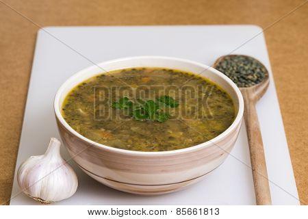 Lentil stew with garlic on white board