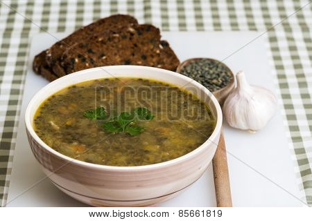 Lentil stew with bread and garlic on white board