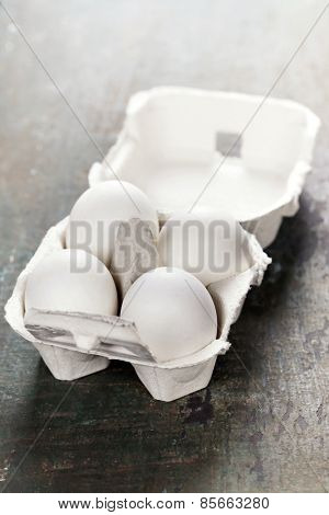 Cardboard egg box with eggs on wooden table