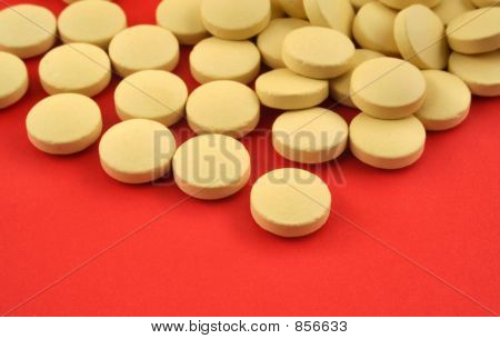 handful of yellow tablets on red 3