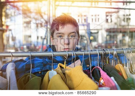 Portrait Of A Teenage Boy Behind A Clothes Rail On A Flea Market