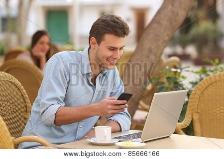 Self Employed Man Working With A Laptop And A Phone In A Restaurant