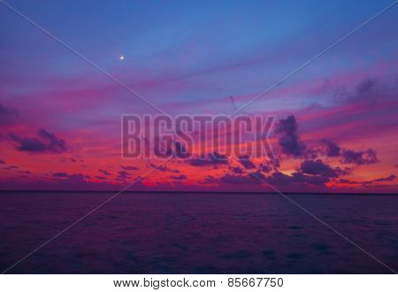 Sunset in the Maldives with a view of the lagoon, beach and bungalows