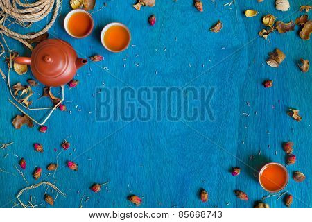 Clay teapot and three teacups with the rope rose buds and shuck on blue wodden background. Top view. Space for text.