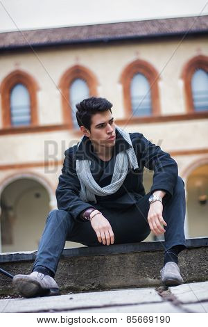 Stylish Trendy Young Man Sitting Outdoor In Old Historical Building