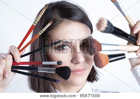 .Applying makeup.Beautiful young woman holding different make up brushes