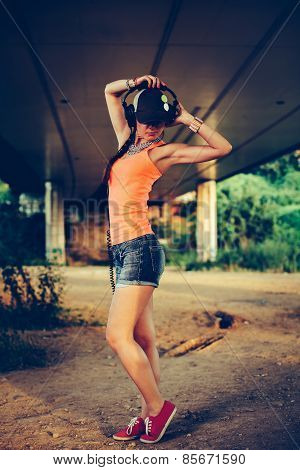 Beautiful Hip Hop Woman With A Cap Which And Headphones Listening To Music