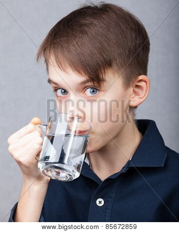 Cute boy drinking water on grey background