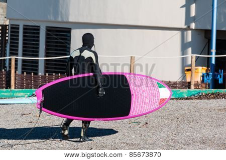 Surfer Black Wetsuit With Pink Board In Winter