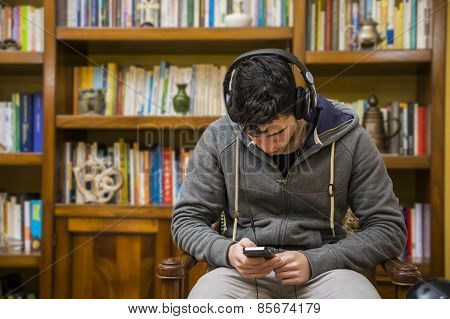 Attractive Young Man Sitting Listening To Music On A Set Of Stereo Headphones