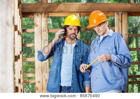 Male architect using mobilephone while standing with colleague at construction site