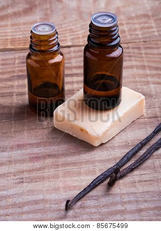Bottles With Aroma Oil, Vanilla Pods And Soap On The Wooden Background