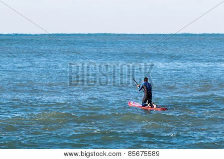 Man Paddleboarding On Red Board, Surfer