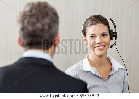 Young female customer service representative wearing headset while looking at manager