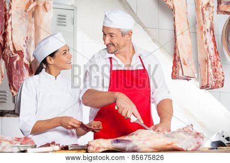 Mature butchers looking at each other while working together at counter in butchery