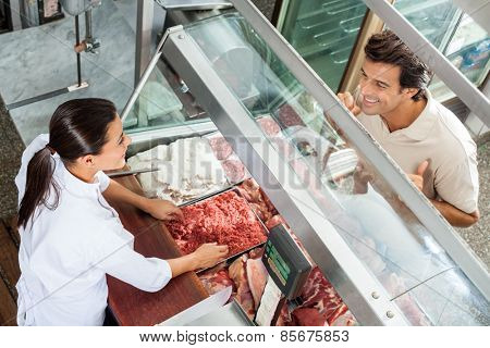 High angle view of female butcher selling minced meat to male customer in butchery