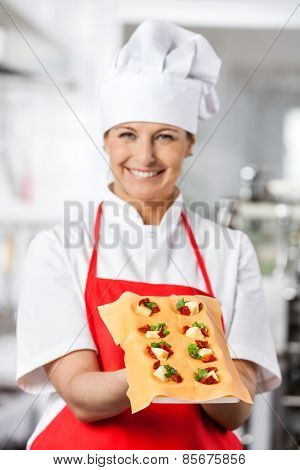 Portrait of beautiful female chef presenting tray with stuffed ravioli pasta sheet in commercial kitchen