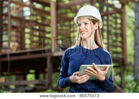 Happy female architect holding digital tablet against incomplete timber cabin at construction site
