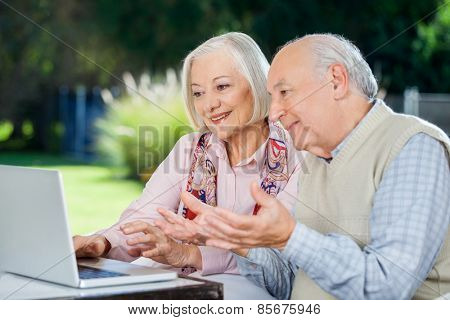 Elderly couple video chatting on laptop while sitting at nursing home porch