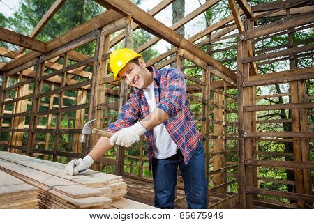 Portrait of confident male construction worker hammering nail on wooden plank at site