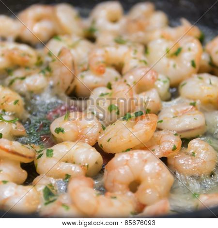 Closeup Of Fried Shrimp With Fresh Herbs On A Frying Pan