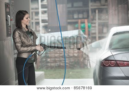 Attractive woman washing automobile at manual car washing self service,cleaning with pressured water