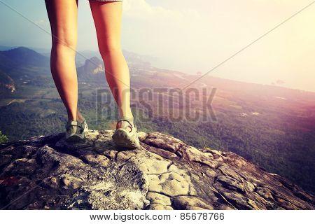 young woman hiker legs climbing at mountain peak rock
