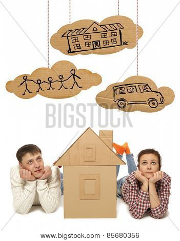 Young couple with the house of cardboard. Photo and hand-drawing elements combined