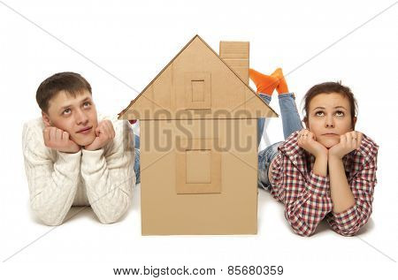 Young couple with the house of cardboard, isolated over a white background