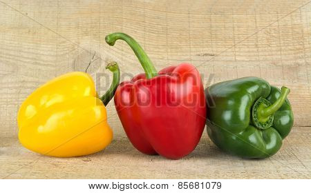 Studio Shot Of Red,yellow,green Bell Peppers On Woden Plank