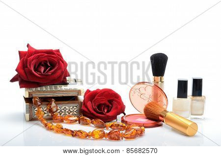 Cosmetics, perfumes, beads, jewelry box and roses in a still life