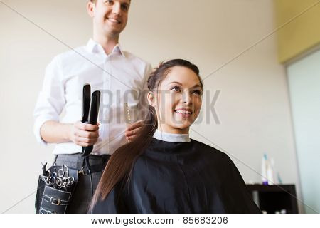 beauty, hairstyle and people concept - happy young woman with hairdresser curling hair and making hairdo at salon