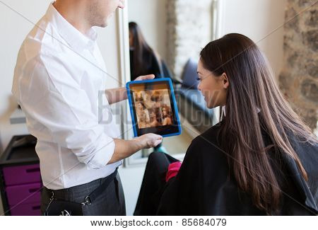 beauty, technology and people concept - happy young woman and stylist with tablet pc computer choosing hairstyle at salon