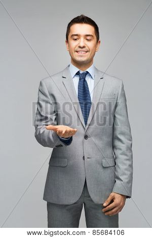 business, people, advertisement and office concept - happy businessman in suit showing or holding something imaginary on empty palms