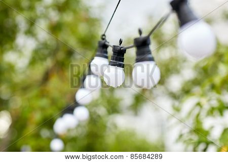 decoration, illumination, electricity, holidays and lightning concept - close up of electric bulb garland hanging in rainy summer garden