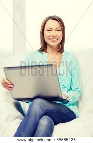 home, technology and internet concept - smiling woman sitting on the couch with laptop computer at home