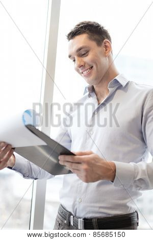 business, construction and office concept - smiling businessman with clipboard in office
