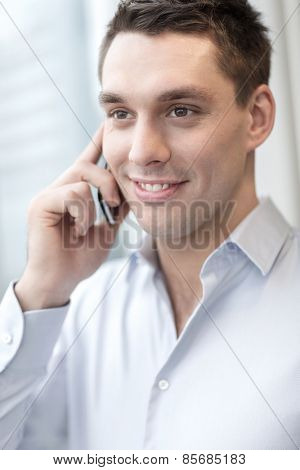 business, technology and office concept - smiling businessman with smartphone in office