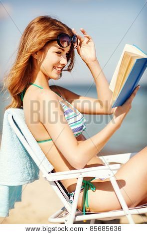 summer holidays and vacation - girl reading book on the beach chair