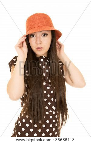 Teen girl wearing a polka dot dress portrait looking at camera adjusting hat