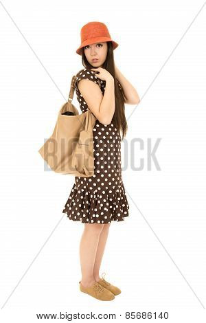 Cute Teen Girl Standing Wearing Polka Dot Dress With A Brown Purse
